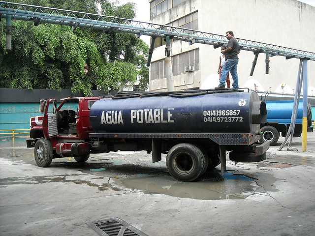 A tanker truck loads water in the El Paraíso neighbourhood on the south side of Caracas, to sell it in poor neighbourhoods or middle-class apartment buildings where the pipes often run dry. Credit: Raúl Límaco/IPS