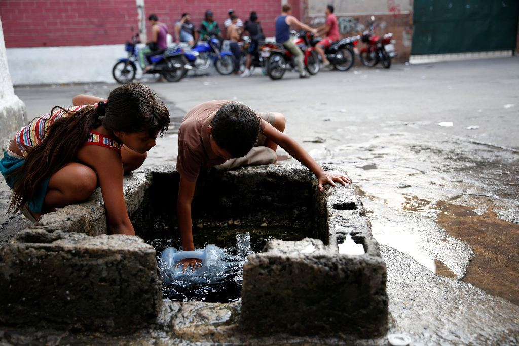 "Children fill plastic containers with water from a well on a street, close to a neighbourhood called ""The Tank"" in the slum of Petare in Caracas, Venezuela, March 17, 2016.Reuters"