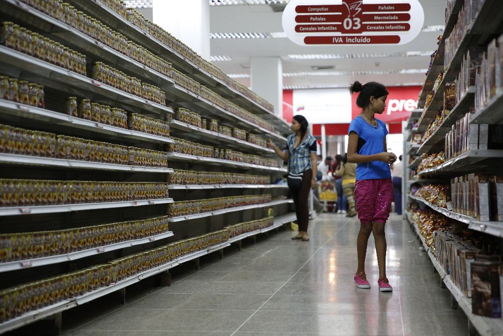 People walk past shelves mostly filled with the same product at a state-run supermarket in Caracas, Venezuela, January 9, 2015.REUTERS/Carlos Garcia Rawlins