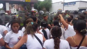 Women confront Venezuelan national guardsmen at a crossing point on Venezuela's border with Colombia. Twitter/@Unaybayona