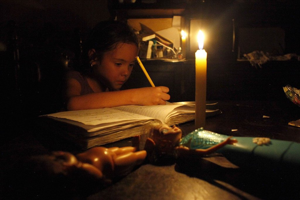 A girl does her homework by candlelight at her home during a power cut in San Cristobal, in the state of Tachira, Venezuela, April 25, 2016. REUTERS/Carlos Eduardo Ramirez