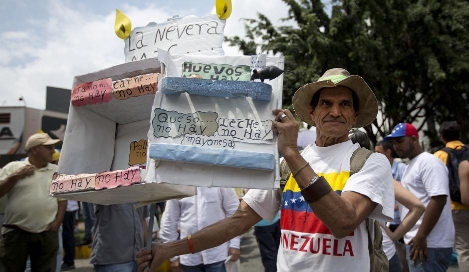 A man shows a cardboard box crafted to depict an empty refrigerator to indicate the shortage of products, during an opposition march in Caracas, Venezuela, Saturday, May 14, 2016. The protesters are demanding that electoral officials accelerate the certification of the petition signatures that would kick off a recall of President Nicolas Maduro. (AP Photo/Ariana Cubillos)