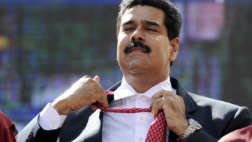 Venezuelan President Nicolas Maduro unties his tie during a rally in Caracas