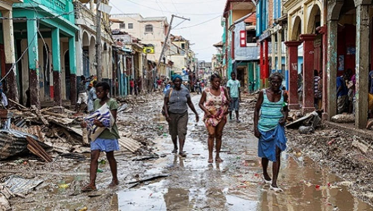 People walk along a street in downtown as clean up from Hurricane Matthew continues in Jeremie, Haiti, October 6, 2016. Picture taken October 6, 2016.