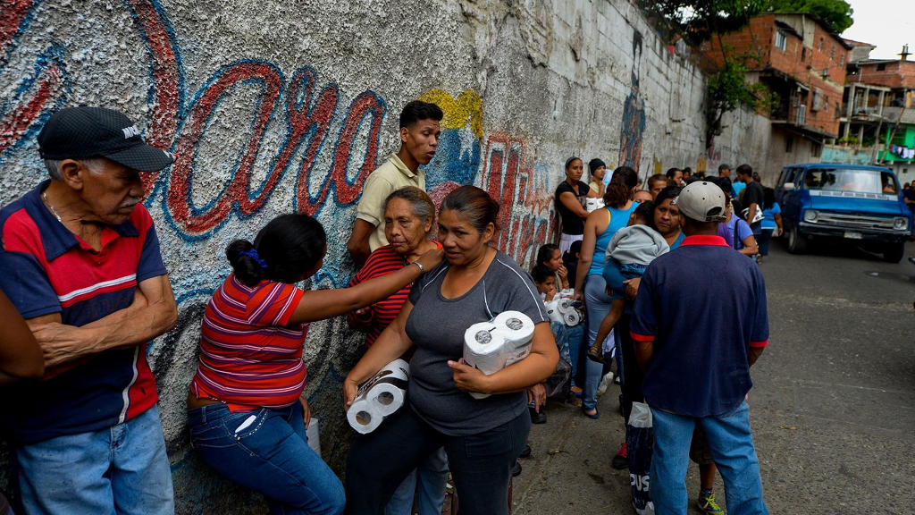 People line up to buy toiletries in a supermarket at Petare neighborhood in Caracas, on June 13, 2016.